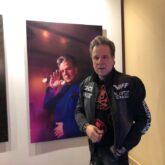 Дмитрий Галихин около своего портрета на выставке в Гостином Дворе